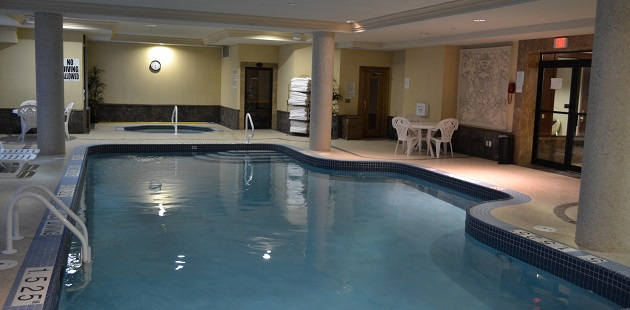 Indoor pool area with towels, seating and a hot tub