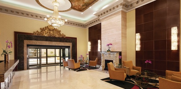 Hotel lobby with a fireplace, armchairs and a Victorian-inspired chandelier
