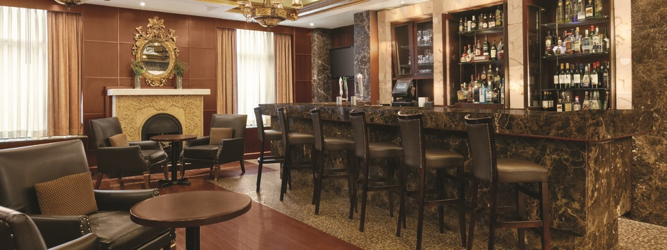 Hotel's Regal Lounge with leather chairs, bar seating and a fireplace