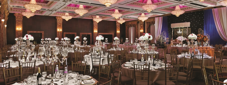Ballroom with ornate flower arrangements and round tables set for a banquet
