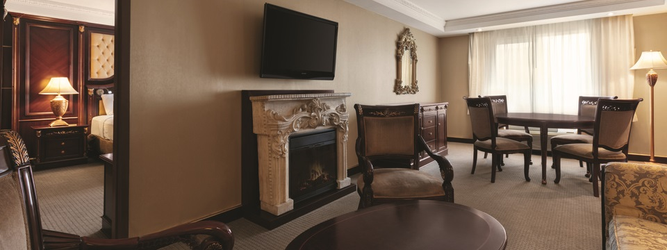 Suite living room with a sofa, two armchairs, a dining area and a flat-screen TV mounted above the fireplace