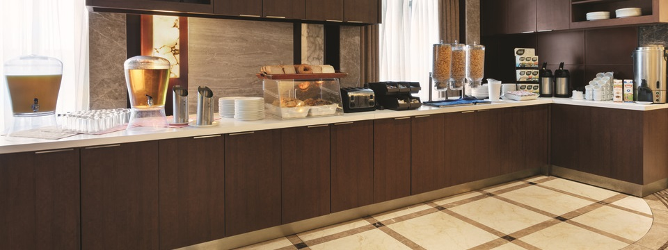 Breakfast area with coffee, juice, cereal and various breads