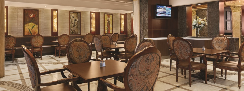 On-site dining area featuring chairs with patterned cushions and paintings of flowers on the wall