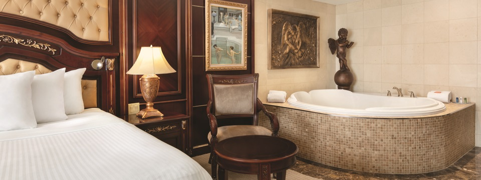 Hotel suite with a king bed, a whirlpool and Victorian-inspired décor