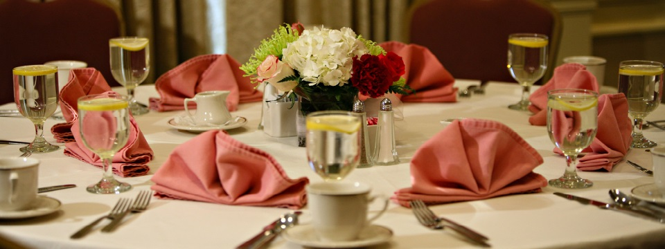 Banquet table settings with a floral centerpiece