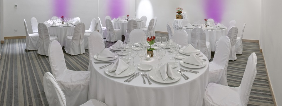 Round tables with all white linens in Concepción event room