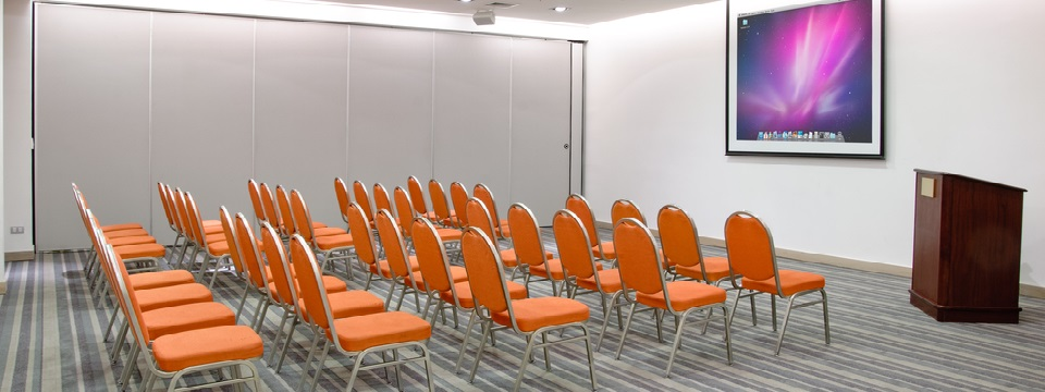 Concepción conference room with white walls and orange chairs