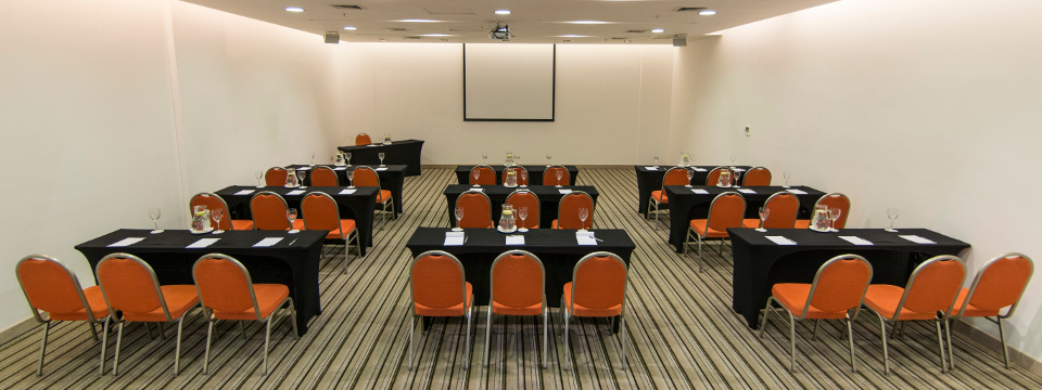 Three rows of tables with three chairs each in event venue