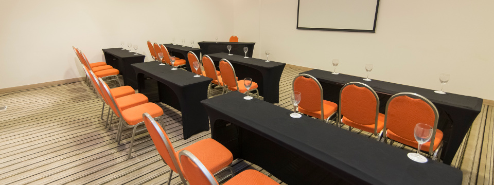 Vibrant orange chairs behind black tables in meeting space