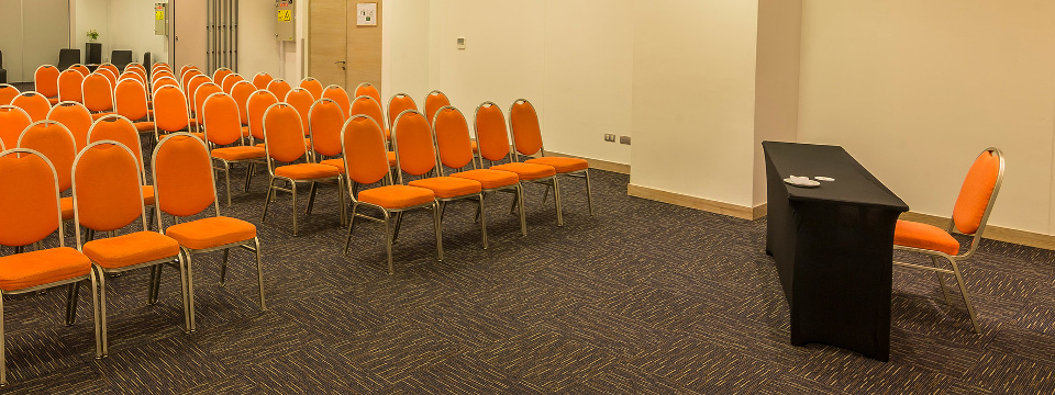 Cloth orange chairs facing head table in meeting room