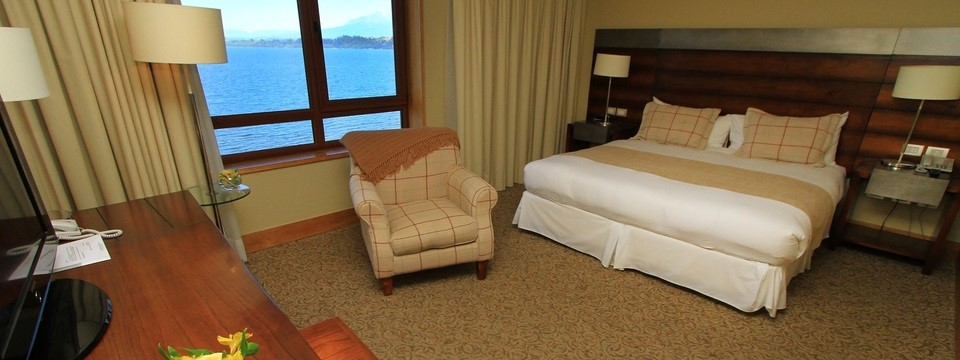 Room with armchair, king bed and view of lake