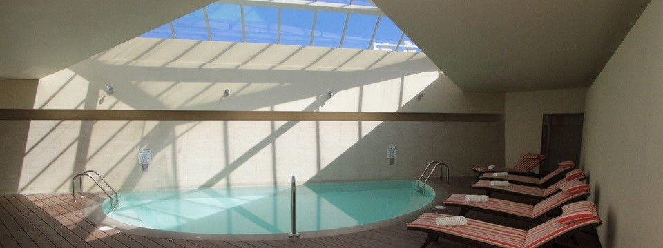 Indoor pool with skylight and chaise lounges