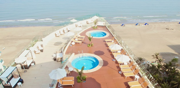 Covered cabanas and two hot tubs on hotel's beachfront terrace