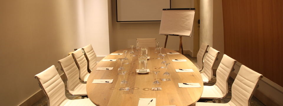 Boardroom with projector screen, flip chart and drinking glasses on table