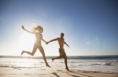 Couple holding hands and running on the beach