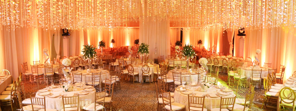 Warmly lit ballroom with strings of jewels hanging from ceiling
