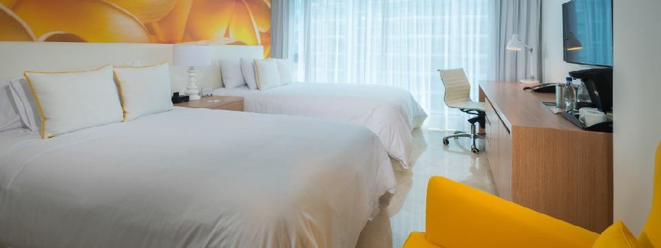 Guest room with two twin beds in front of yellow abstract mural