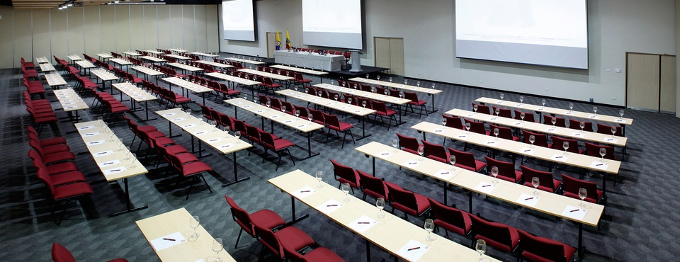 Rows of tables and chairs in meeting room with three projection screens