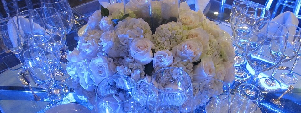 Place settings with glassware and white roses
