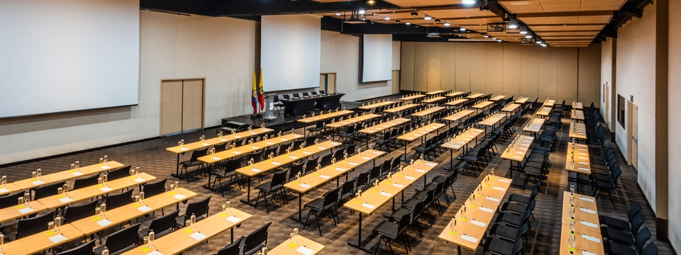 Meeting space with rows of tables and chairs facing projector screens