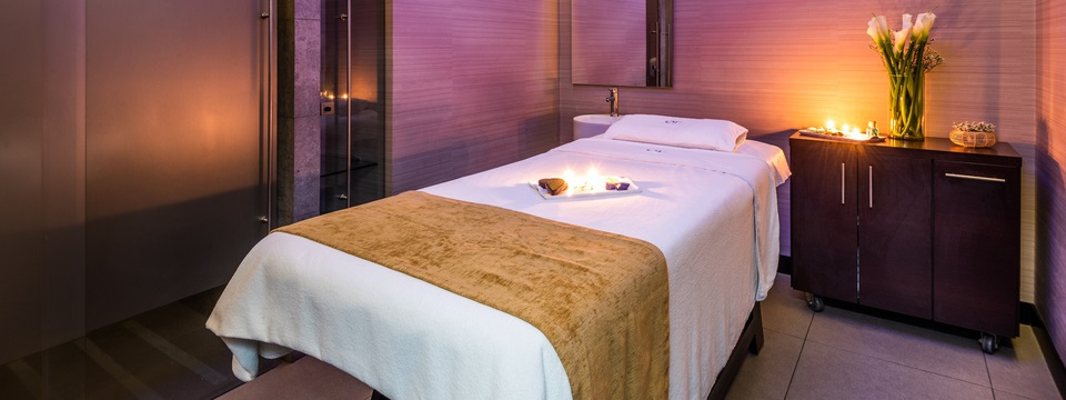 Spa room with a massage table, candles and flowers