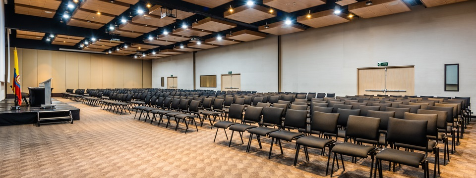 Expansive meeting space with rows of chairs facing presentation screens