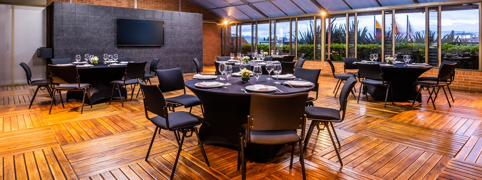 Naturally lit meeting space with round tables and black chairs