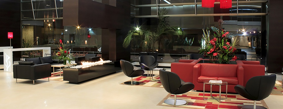 Modern lobby with a fire pit and red and black seating
