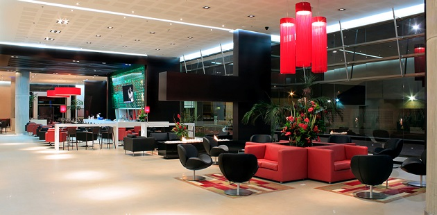 Modern lobby with red couches, black chairs and flowers