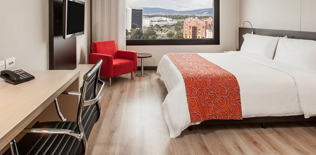 Spacious Bogotá hotel room with city views, flat-screen TV and red accents
