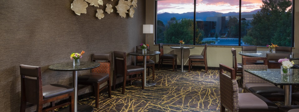 On-site dining room with patterned carpet and a view of the sun setting over the mountains