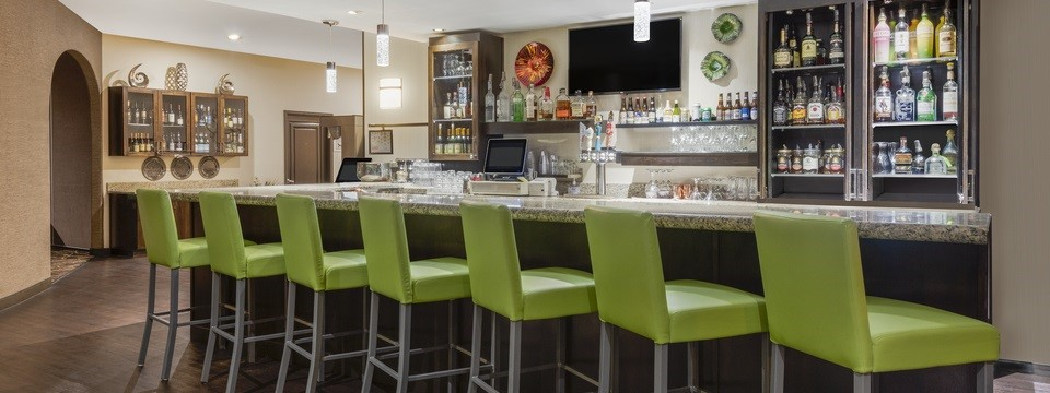 Hotel bar area featuring green stools and a flat-screen TV