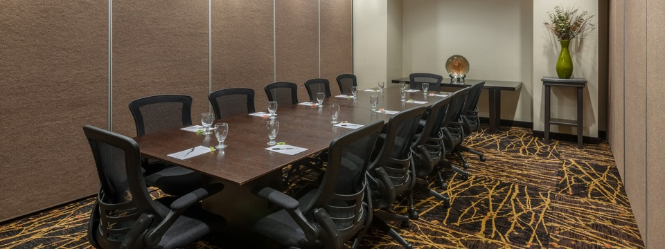 Spacious boardroom with a long wooden table, black chairs and patterned carpet
