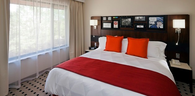 King bed with white sheets, red accent pillows and throw blanket