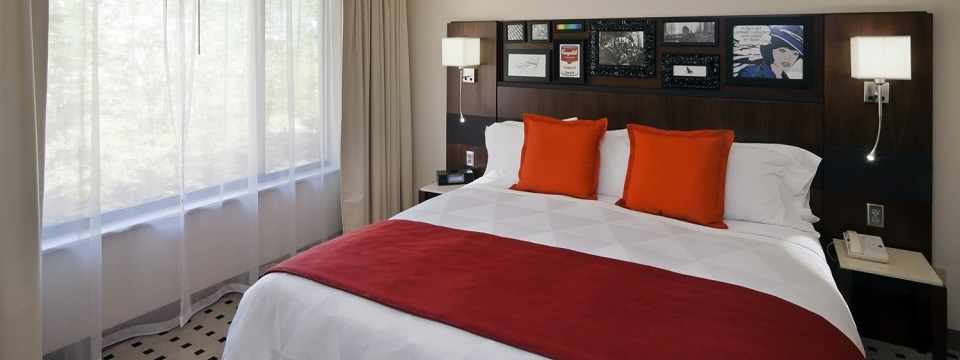 King bed with white bedding, red throw pillows and blanket