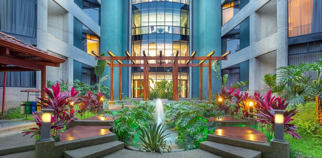 San Jose hotel exterior with water fixtures and greenery