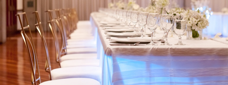 Centerpieces with white flowers and crystal glasses arranged on a table