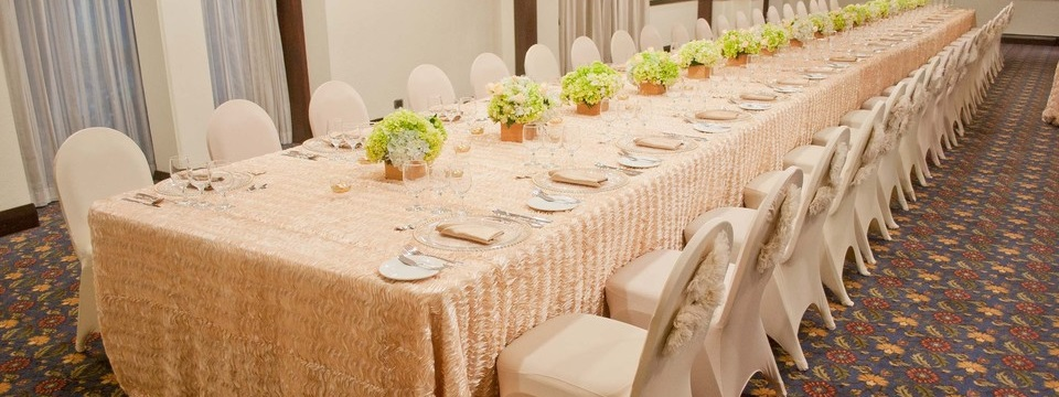 Long table with glassware and floral arrangements