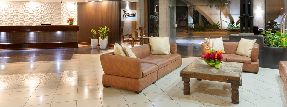 Hotel front desk and lobby area with comfortable couches