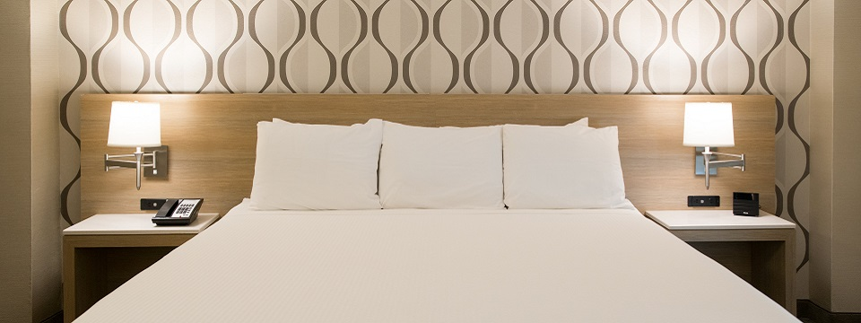 King bed against a modern, built-in headboard with matching side tables