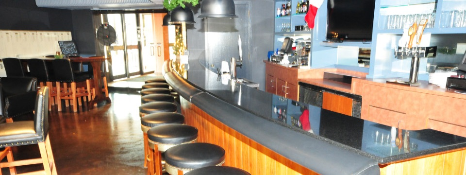 Bar with stools and tall tables and chairs covered in black leather