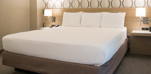 Hotel room with a king bed against a modern built-in headboard