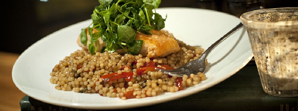 A plate of couscous topped with fish and greens