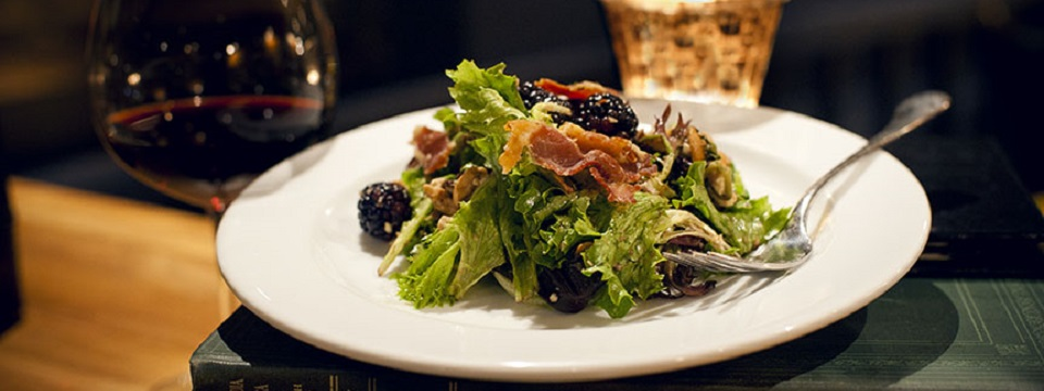 Salad plate with greens, blackberries and sliced cured meat