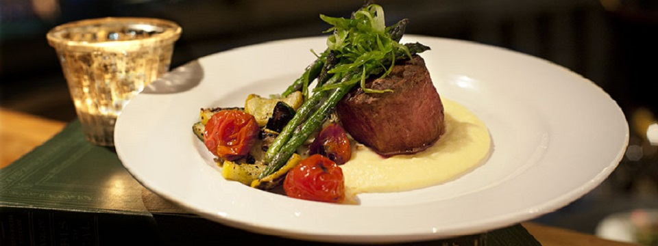 A steak plated atop a puree with roasted vegetables on the side