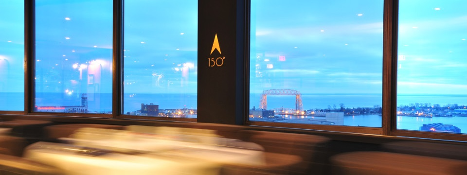 Restaurant windows overlooking the Duluth harbor at dusk
