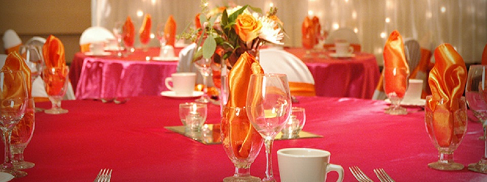 Round table covered in pink tablecloth set with water glasses and coffee mugs