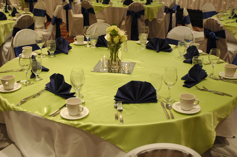 Round tables covered in green and white linens with water glasses and wine glasses