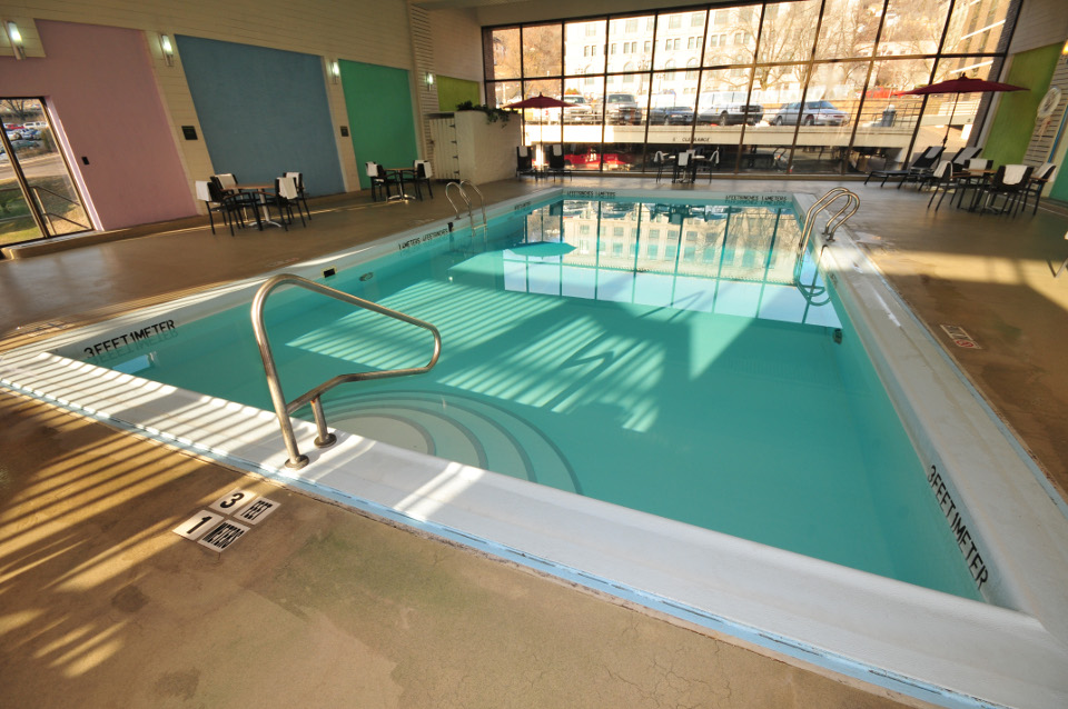Indoor pool area with large windows looking out onto city street