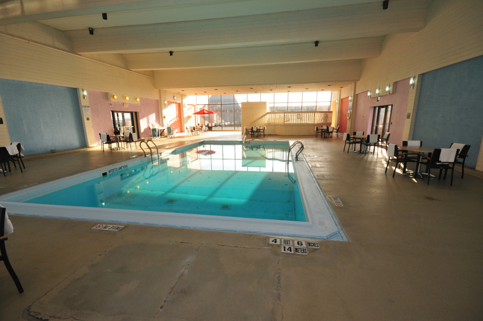 Hotel's indoor swimming pool area with chairs and tables